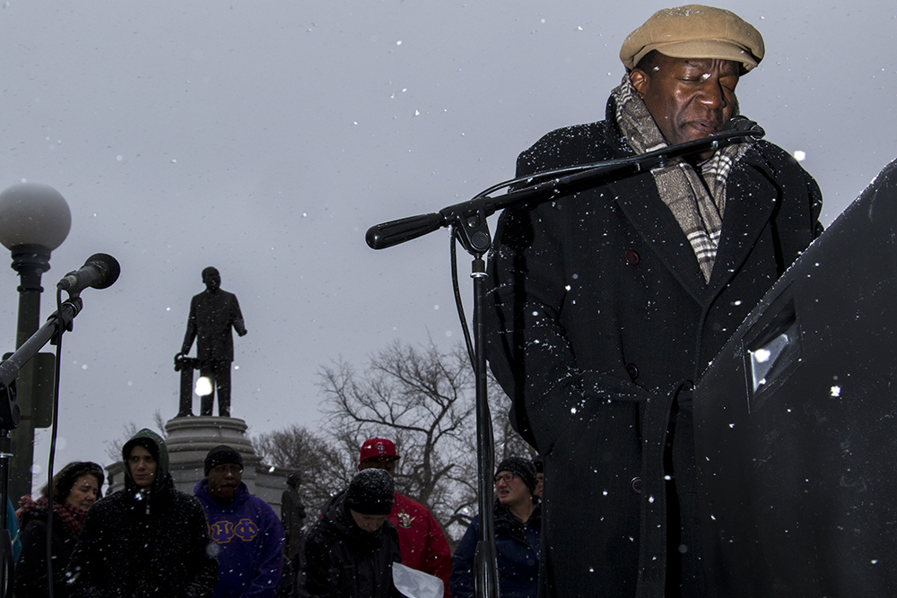 Dr. Gregory McDonald leads an opening prayer at City Park. The Martin Luther King Jr. Day Marade, Jan. 15, 2018. (Kevin J. Beaty/Denverite)  mlk; martin luther king jr; marade; parade; march; denver; colorado; denverite; protest; city park;
