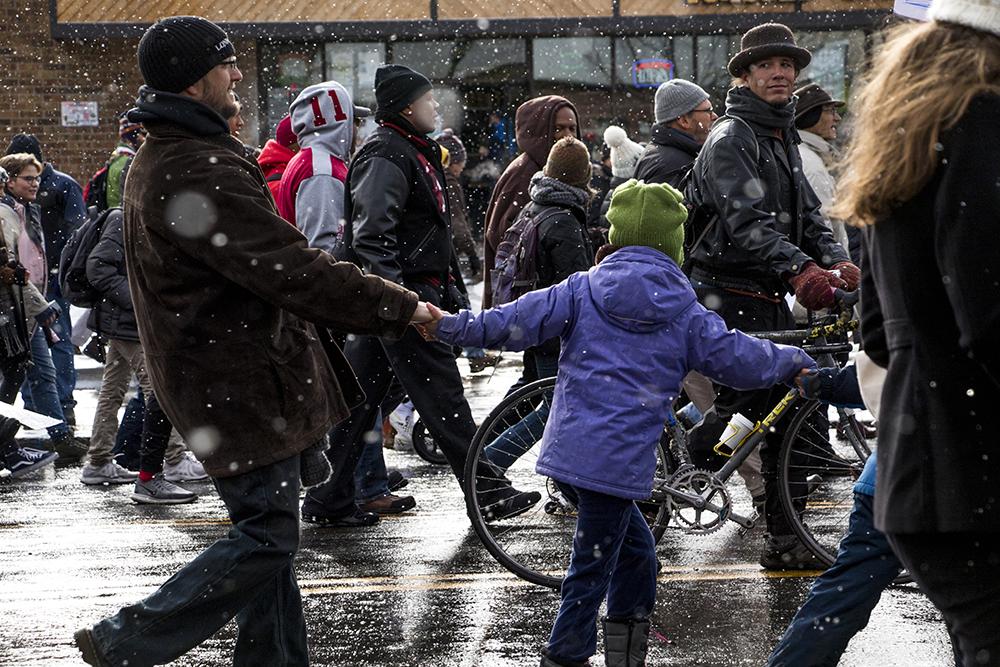 The Johnsen-Sammen family marches with linked hands. The Martin Luther King Jr. Day Marade, Jan. 15, 2018. (Kevin J. Beaty/Denverite)  mlk; martin luther king jr; marade; parade; march; colfax; denver; colorado; denverite; protest;