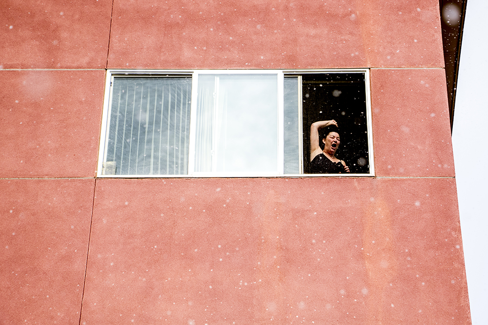 A woman hollers from her window above the Martin Luther King Jr. Day Marade, Jan. 15, 2018. (Kevin J. Beaty/Denverite)  mlk; martin luther king jr; marade; parade; march; colfax; denver; colorado; denverite; protest;