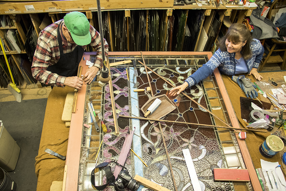 Phil and Jane Watkins and a window from the Molly Brown House in their Englewood workshop, Jan. 18, 2018. (Kevin J. Beaty/Denverite)  englewood; colorado; denverite; watkins stained glass; kevinjbeaty; artists;