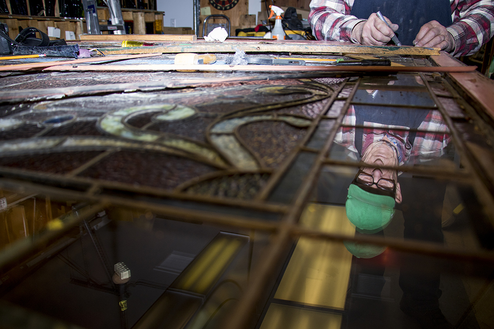 Phil Watkins at work on a window possibly made by his great-grandfather for the Molly Brown House. The workshop at Watkins Stained Glass, Jan. 18, 2018. (Kevin J. Beaty/Denverite)  englewood; colorado; denverite; watkins stained glass; kevinjbeaty; artists;