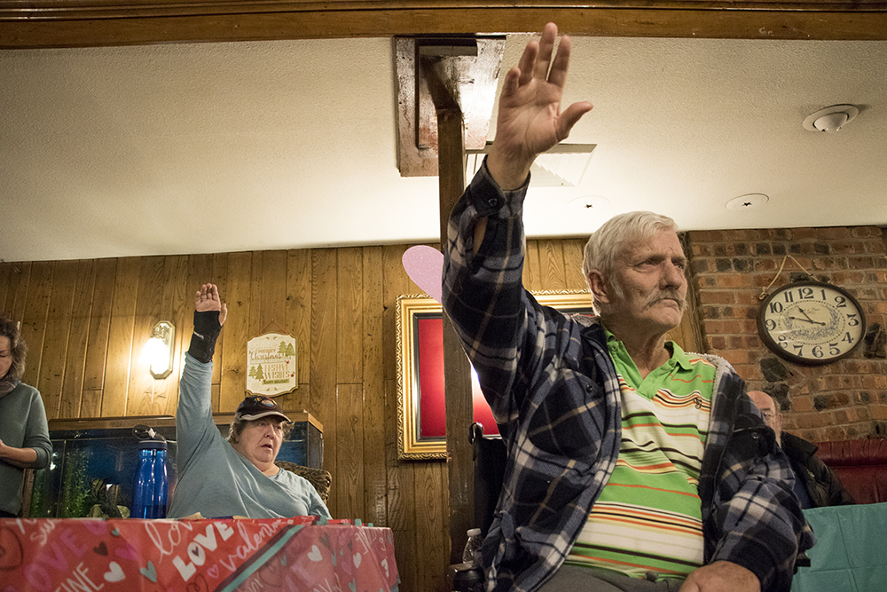 Charles Prigee (right) and Kristina Petersen raise their hands to ask questions. A meeting informing Golden Manor residents on details for the assisted living facility's closure in three months, Jan. 25, 2018. (Kevin J. Beaty/Denverite)  assited living; aging; affordable housing; housing; elder care; denver; denverite; west colfax; kevinjbeaty;