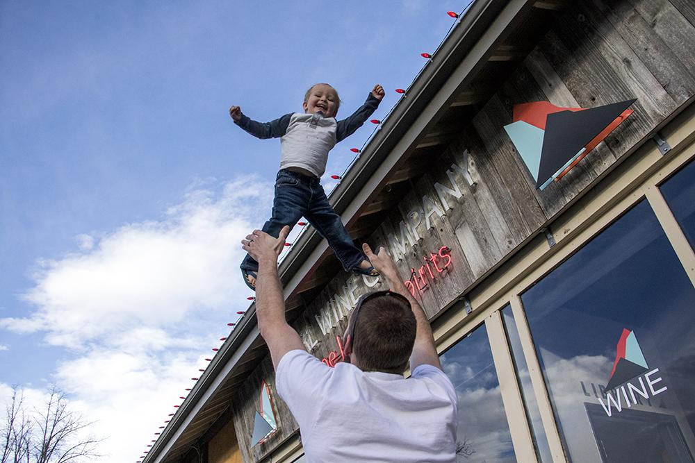Paul Hurst launches two-year-old Tabor into the air. South Pearl Street, Platt Park. Jan. 30, 2018. (Kevin J. Beaty/Denverite)  denver; colorado; denverite; kevinjbeaty; platt park; kids;