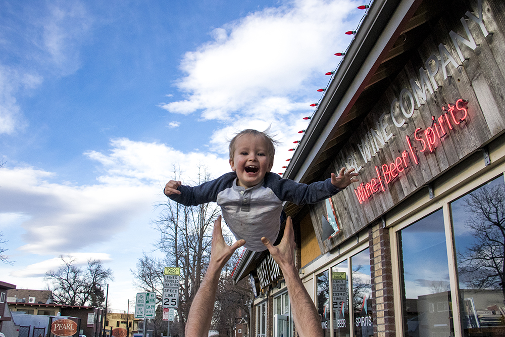 Paul Hurst launches two-year-old Tabor into the air. South Pearl Street, Platt Park. Jan. 30, 2018. (Kevin J. Beaty/Denverite)