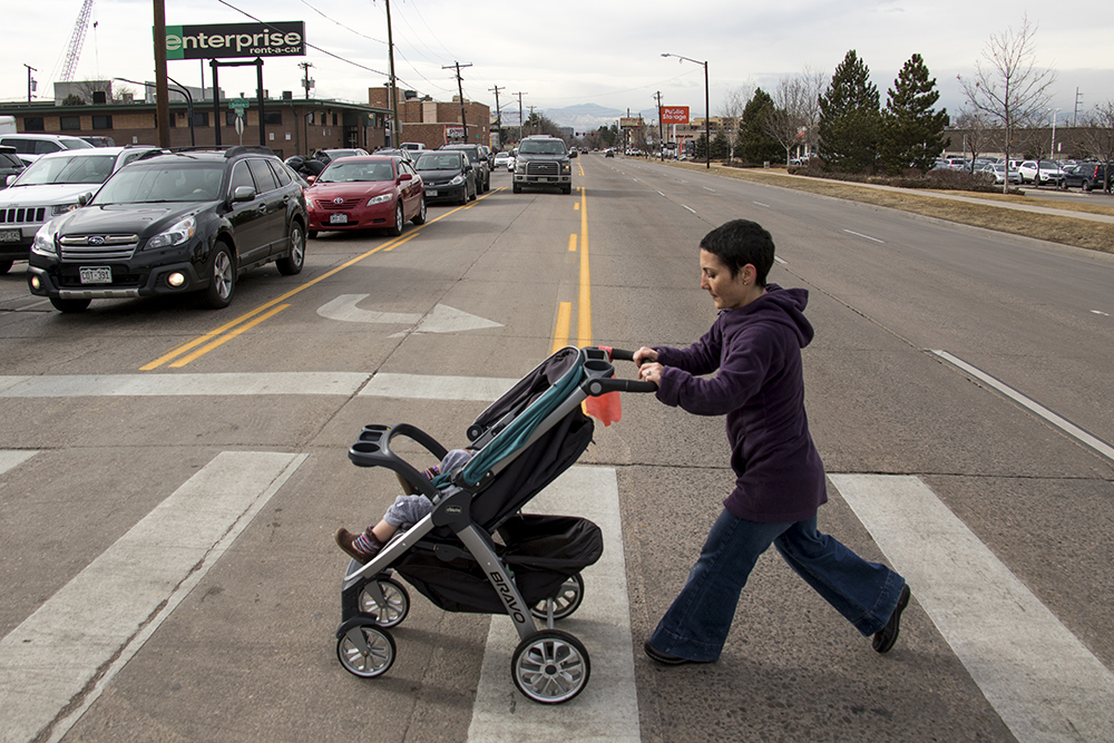 Jody Davison crosses Evans Avenue in University Hills, Jan. 31, 2018. (Kevin J. Beaty/Denverite)  denver; colorado; denverite; kevinjbeaty; pedestrians; university hills; sidewalks;