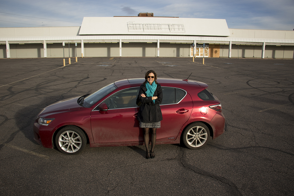 District 4 Councilwoman Kendra Black leans against her red Lexus in front of a long-shuttered K-Mart at the corner of Evans Avenue and Monaco Parkway, Jan. 31, 2018. (Kevin J. Beaty/Denverite)  city council; goldsmith; denver; denverite; colorado; kevinjbeaty;