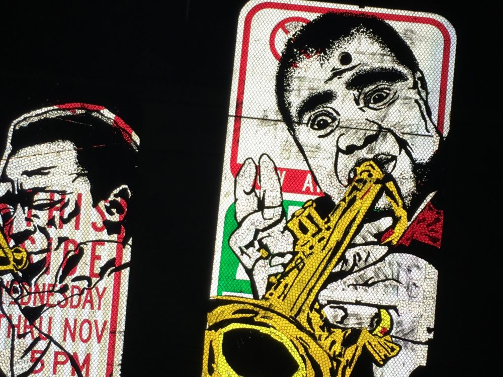 Illustrations of Miles Davis and Louis Armstrong by Dan Ericson on street signs illuminated by a camera flash. (Andrew Kenney/Denverite)