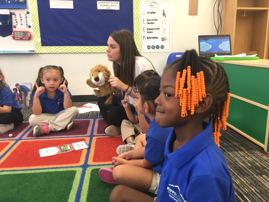 "Caroline Hiskey, a preschool teacher at KIPP Northeast Elementary in Denver, reviews letters with the help of ""Phonics Lion."" (Chalkbeat)"