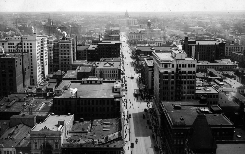 """An aerial view of 16th Street circa 1910-1920. hows the downtown business district, the Arapahoe County Courthouse, Cathedral of the Immaculate Conception, Joslin's Dry Goods and the Colorado State Capitol Building. Signs read: """"The May Co."""", """"The National Safety Vault Company"""", """"Joslin's Dry Goods"""", """"Douglas Shoe Co."""" and """"M Philipsborn & Co."""". (Harry Mellon Rhoads/Western History & Genealogy Dept.Denver Public Library)"""