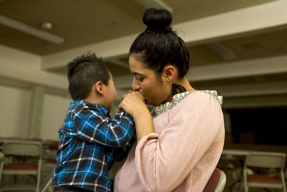 Araceli Velasquez comforts her son, Christopher, who's hurt his finger. Park Hill United Methodist Church and Temple Micah, Jan 20, 2018. (Kevin J. Beaty/Denverite)  immigration; denver; colorado; undocumented; tps; south park hill; denverite; kevinjbeaty;