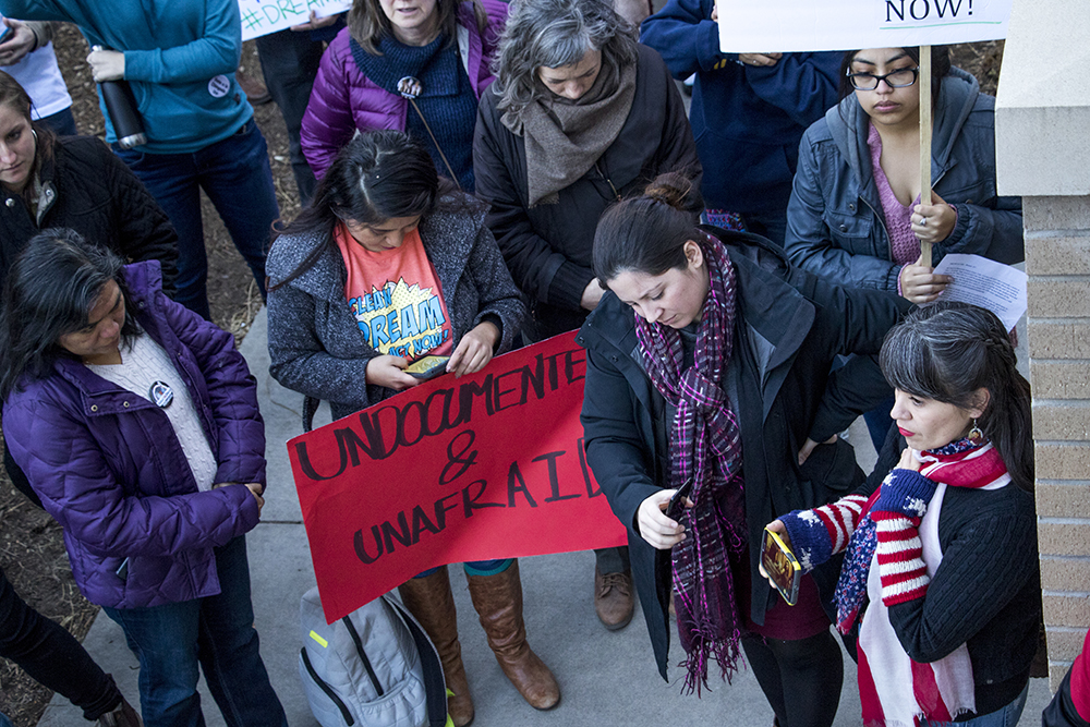 Corrine Rivera-Fowler, organizer with Padres & Jóvenes Unidos, holds a live stream of protesters occupying Sen. Michael Bennet's office as ralliers gather outside, Feb. 7, 2018. (Kevin J. Beaty/Denverite)