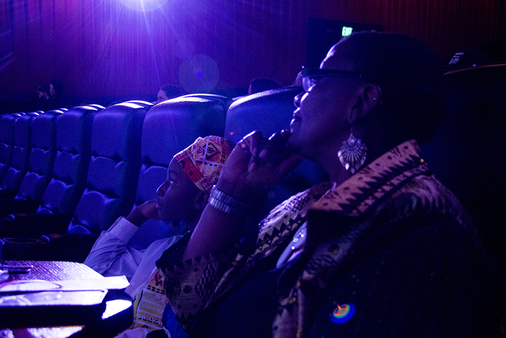 9-year-old Shamar and his grandmother, Josephine Conner, wait for the program to begin. Black Panther opens in Denver at Alamo Draft House Cinema on West Colfax, Feb. 16, 2018. (Kevin J. Beaty/Denverite)  movie theater; alamo draft house cinema; black panther; denverite; denver; colorado; kevinjbeaty;