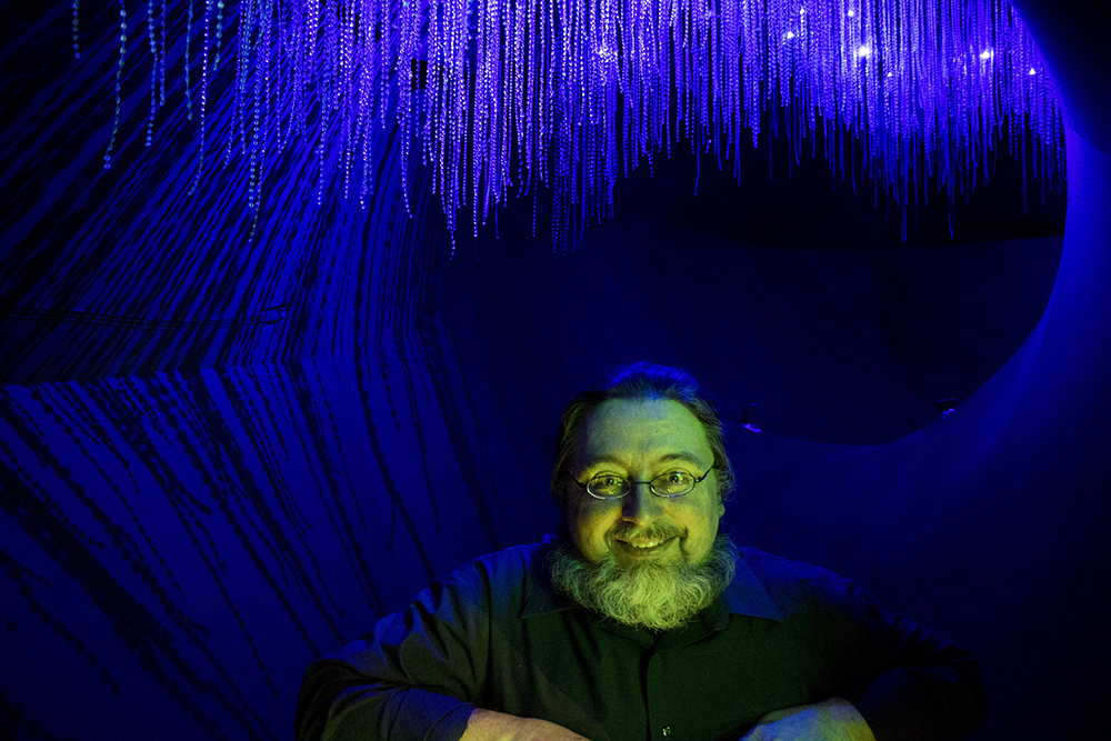 """Dr. Frank Krell poses inside a part of the """"Creatures of Light,"""" exhibit at the Denver Museum of Nature and Science, Feb. 15, 2018. (Kevin J. Beaty/Denverite)"""