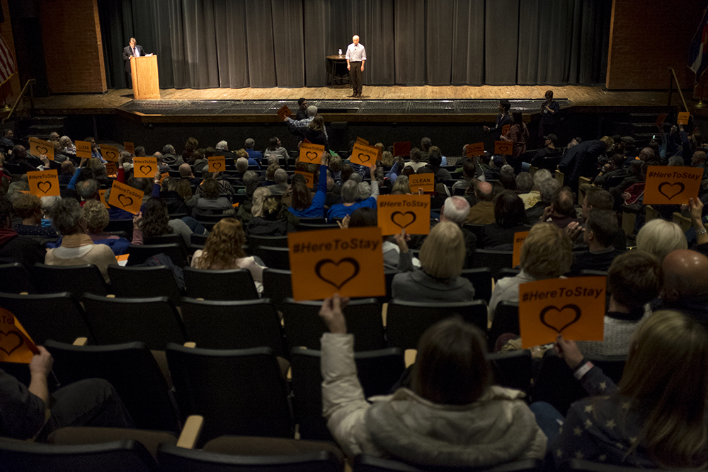 """The crowd holds signs for a """"clean DREAM act"""" as Mike Coffman speaks at a town hall event at Cherry Creek High School, Feb. 21, 2018. (Kevin J. Beaty/Denverite)  copolitics; town hall; mike coffman; greenwood village; denver; colorado; denverite; kevinjbeaty;"""