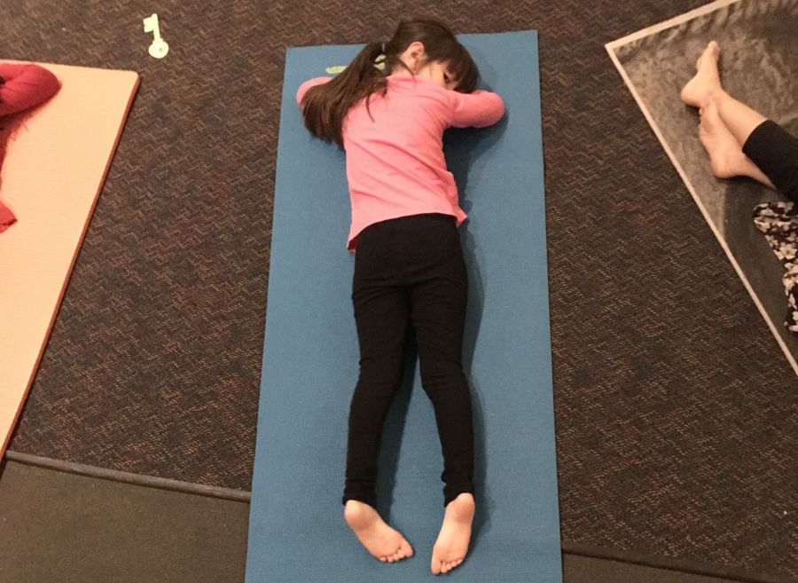 A girl rests at the end of yoga club at Doull Elementary in Denver. (Melanie Asmar/Chalkbeat)