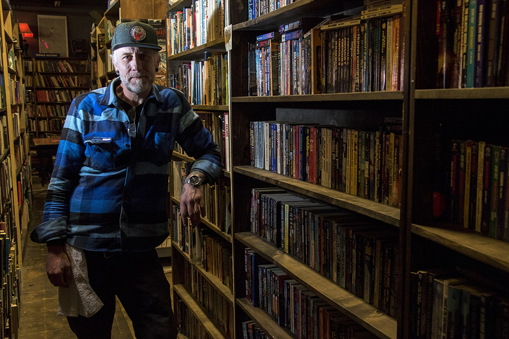 Mutiny Information Cafe owner Jim Norris among his bookshelves, March 8, 2018. (Kevin J. Beaty/Denverite)  south broadway; denver; denverite; kevinjbeaty; colorado;