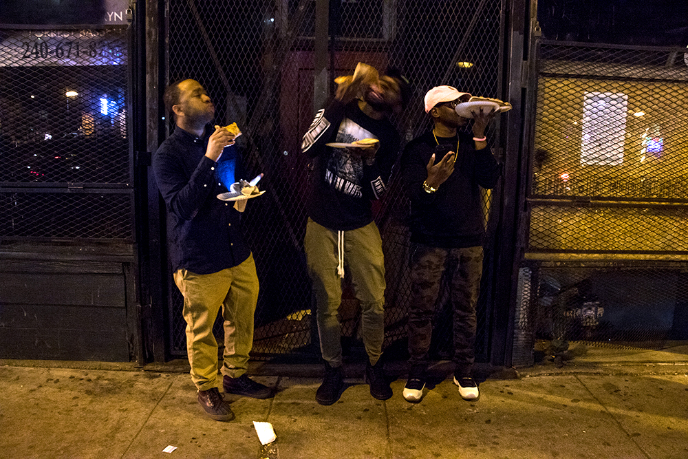 Tony Range (left to right), Tyrell Harvey and Maurice Brown munch on pizza after closing time in LoDo, March 12, 2018. (Kevin J. Beaty/Denverite)