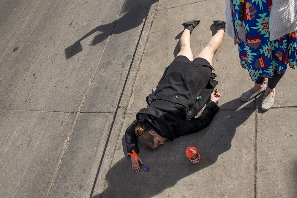 """Lee Kucic on the ground during a """"die-in"""" in protest against gun violence, Mach 14, 2018. (Kevin J. Beaty/Denverite)  protest; rally; denver; valverde; denverite; kevinjbeaty; colorado;"""