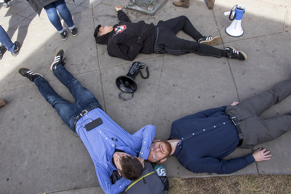 """Ian Broderick (counterclockwise), Jake Wunsh and Mateo Manuel Vela lie during a """"die-in,"""" part of a school walkout in protest against gun violence, Mach 14, 2018. (Kevin J. Beaty/Denverite)  protest; rally; denver; valverde; denverite; kevinjbeaty; colorado;"""