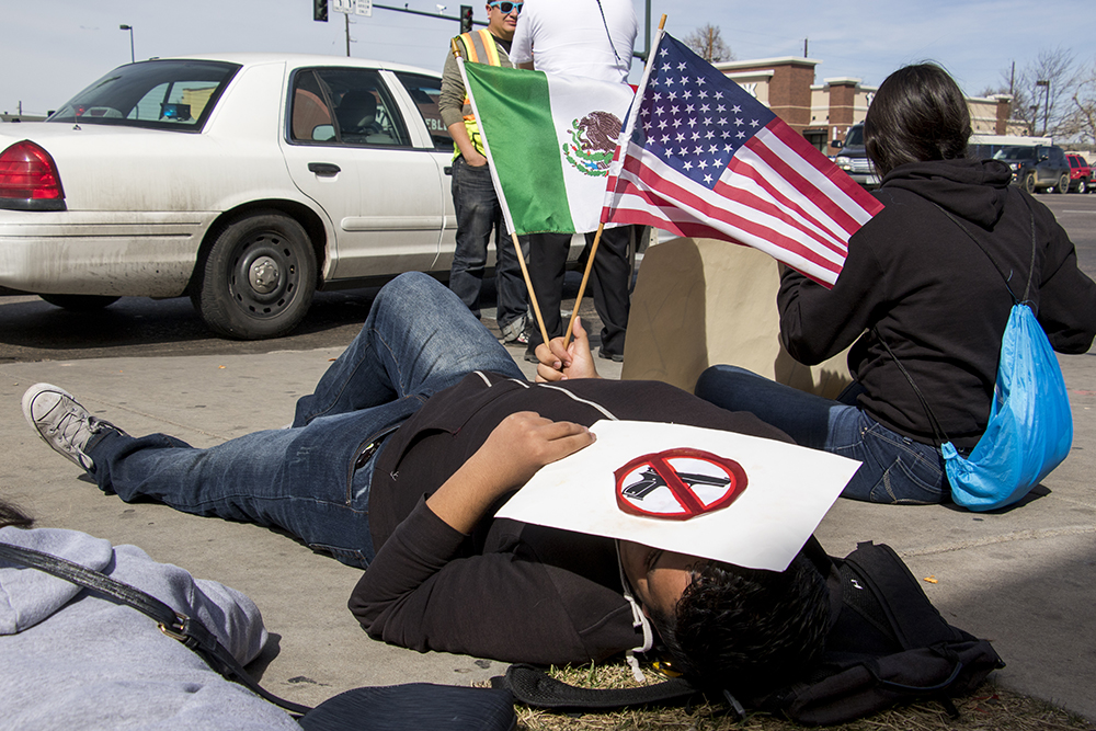 """A student named Max lies with a Mexican and American flag during a """"die-in,"""" part of a school walkout in protest against gun violence, Mach 14, 2018. (Kevin J. Beaty/Denverite)  protest; rally; denver; valverde; denverite; kevinjbeaty; colorado;"""