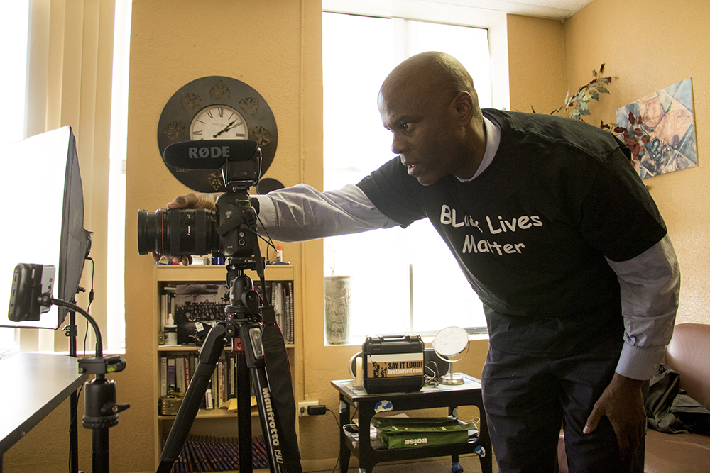 """Brother Jeff Fard prepares to film and stream """"30 Minutes With Brother Jeff"""" in his Welton Street office, March 15, 2018. (Kevin J. Beaty/Denverite)"""