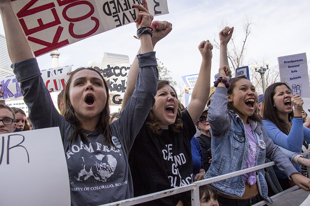 Ellie Creasey (left to right), Sydney Stegeman and Taylor Bray, all 17, cheer during the March For Our Lives at Civic Center Park, March 24, 2018. (Kevin J. Beaty/Denverite)  protest; rally; gun violence; gun control; kevinjbeaty; denver; denverite; colorado;