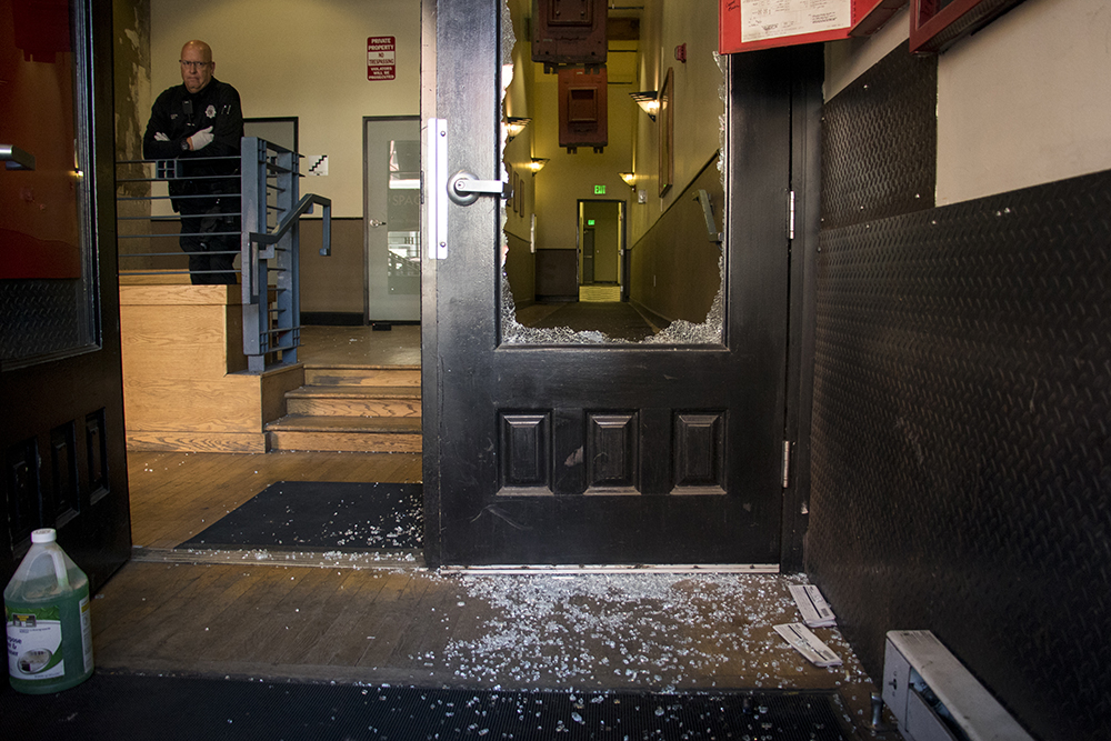 A broken window and a Denver Police officer inside the Studebaker Lofts at 1510 Blake Street, April 3, 2018. (Kevin J. Beaty/Denverite)  crime; downtown; denver; police; colorado; kevinjbeaty; denverite;
