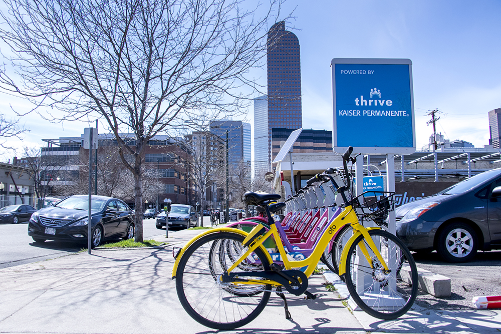 An Ofo bike parked next to a B-cycle station on 17th Avenue, April 15, 2018. (Kevin J. Beaty/Denverite)  denver; colorado; denverite; kevinjbeaty; bike share; ofo; b cycle; bicycle; bike; transportation;