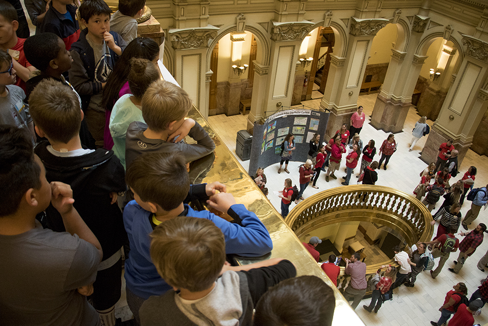 Fourth graders from Creekside Elementary on a tour of the Colorado State Capitol look down as teachers who have walked out of class enter to protest a lack of school funding, April 16, 2018. (Kevin J. Beaty/Denverite)  denver; colorado; protest; education; teacher strike; denverite; kevinjbeaty; teachers;