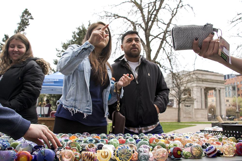 Ashley Castillo and Jose Yitbos peruse glassware at Denver's 2018 Mile High 420 Festival, April 20, 2018. (Kevin J. Beaty/Denverite)  420; stoner; denver; denverite; colorado; kevinjbeaty;