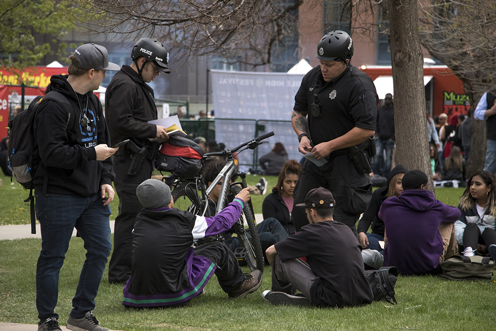 Denver Police officers write public consumption tickets. Denver's 2018 Mile High 420 Festival, April 20, 2018. (Kevin J. Beaty/Denverite)