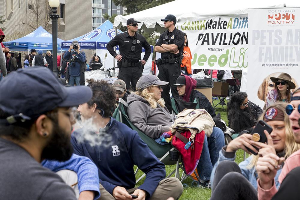 Denver Police officers stand on patrol as people smoke marijuana during Denver's 2018 Mile High 420 Festival, April 20, 2018. (Kevin J. Beaty/Denverite)  420; stoner; denver; denverite; colorado; kevinjbeaty;