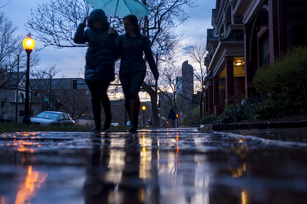 Kristin Bietsch (left) and Michelle Weinberger walk under an umbrella during a spring shower, April 23, 2018. (Kevin J. Beaty/Denverite)  rain; weather; cowx; spring; denver; colorado; sunset; evening; denverite; kevinjbeaty;