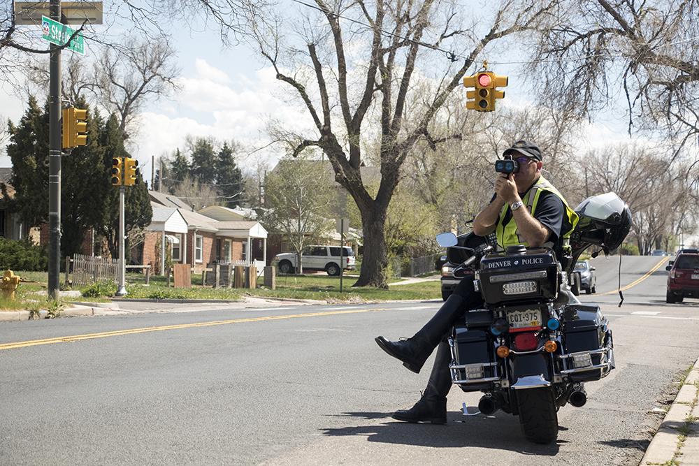 Officer George Gann enforces the speed limit in a school zone  on Steele Street, April 23, 2018. (Kevin J. Beaty/Denverite)