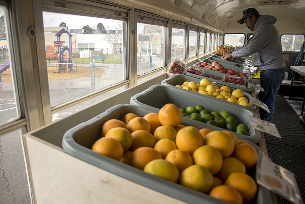 Jorge Martinez shops inside Any Street Grocery, which is currently parked at McGlone Academy, an elementary school in Montbello, April 24, 2018. (Kevin J. Beaty/Denverite)