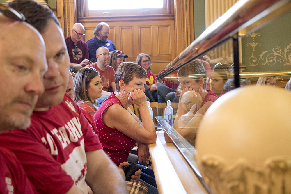 Deb Park, a K-5 reading specialist, peers down at in Senate chamber. Protesters watch the state House of Representatives on a day of protest of a lack of funding for schools, April 27, 2018. (Kevin J. Beaty/Denverite)  redfored; education; teachers; protest; denver; colorado; denverite; kevinjbeaty;