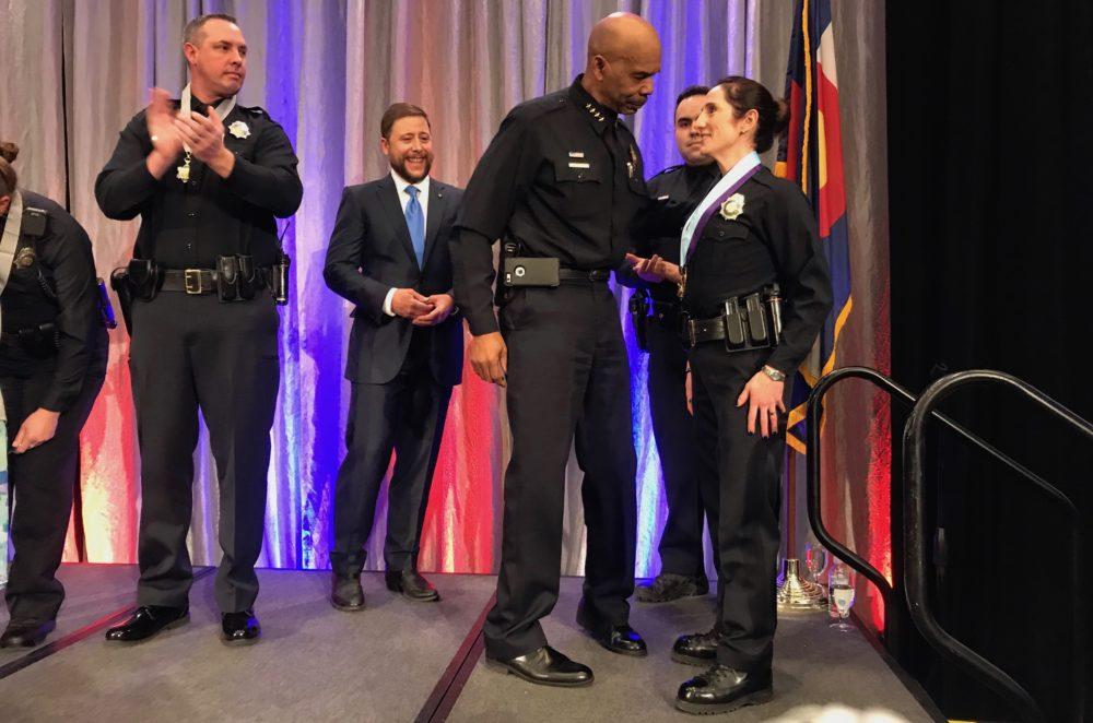 Denver police Det. Rachel Eid shakes hands with Chief Robert C. White after receiving the department's Medal of Honor on Thursday, April 19, in downtown Denver. Esteban L. Hernandez / Denverite