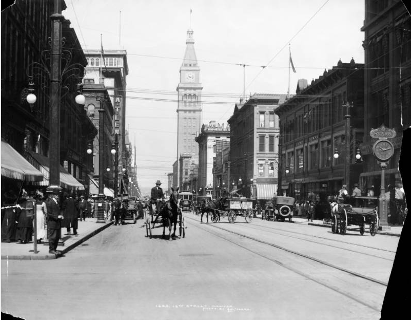 """View of 16th (Sixteenth) Street in Denver, Colorado; shows pedestrians, traffic, automobiles, a streetcar, and horse drawn buggies and wagons. Street lights, a clock and the Daniels & Fisher Tower line the sidewalks; signs read: """"Starr"""" and """"Gano Downs."""" (Denver Public Library/History Colorado Collection/CHS.X5354)"""
