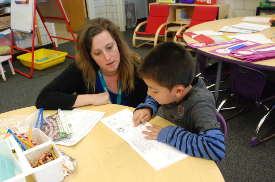 Kim Ursetta works with a student in her classroom at Denver's Mathematics and Science Leadership Academy. (Ann Schimke/Chalkbeat)