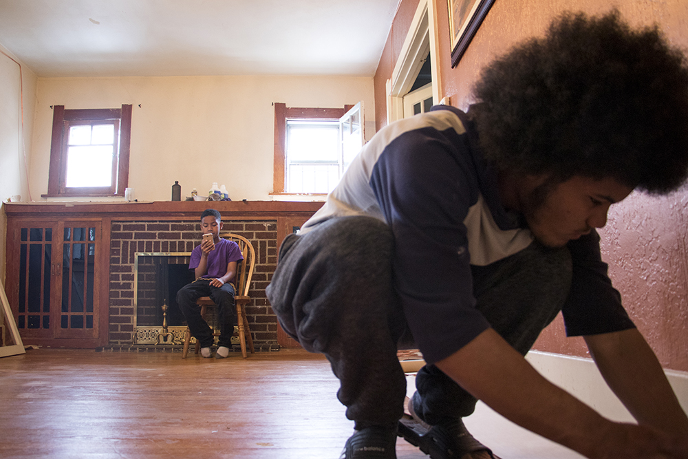 Elijah Beauford's nephew,  Amier, plays on his phone as Beauford strips paint from the baseboards in his father's house, April 29, 2018. (Kevin J. Beaty/Denverite)  denver; colorado; denverite; kevinjbeaty; skyland; home improvement;