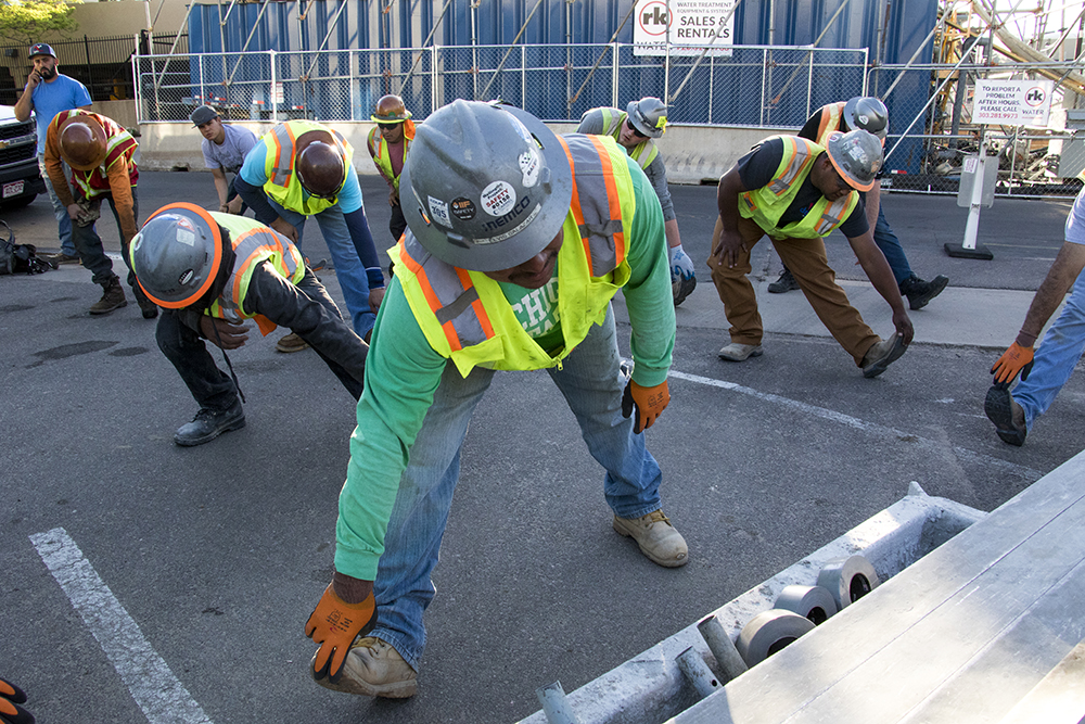Elvis Salazar, who works for Baker Concrete, stretches before the first major slab pour on the Cherry Creek Medical Center at 1st Avenue and Cook Street, May 10, 2018. (Kevin J. Beaty/Denverite)  denver; colorado; denverite; kevinjbeaty; construction; cherry creek; development;