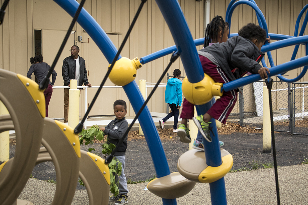 Ashton Kynard tries to round up kids on a playground for a session during the Black Parent Empowerment Summit at Shorter Community AME Church, May 12, 2018. (Kevin J. Beaty/Denverite)