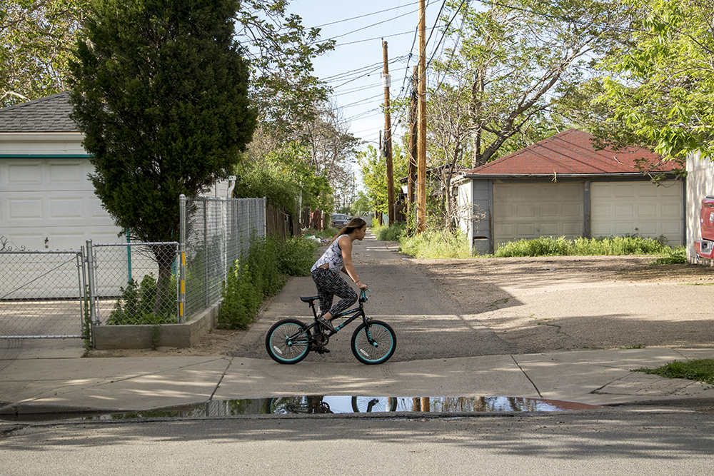 A woman rides a bike in Elyria-Swansea, May 15, 2018. (Kevin J. Beaty/Denverite)  denver; colorado; denverite; kevinjbeaty; elyria swansea; development; gentrification;