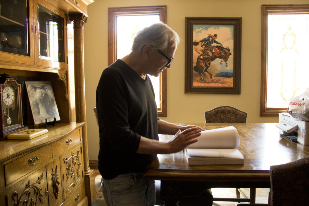 Marshall Fogle thumbs through his biography of General Maurice Rose, namesake of the hospital near Colorado Boulevard, May 17, 2018. (Kevin J. Beaty/Denverite)  denver; colorado; denverite; baseball; sports; collecting; collector; kevinjbeaty;