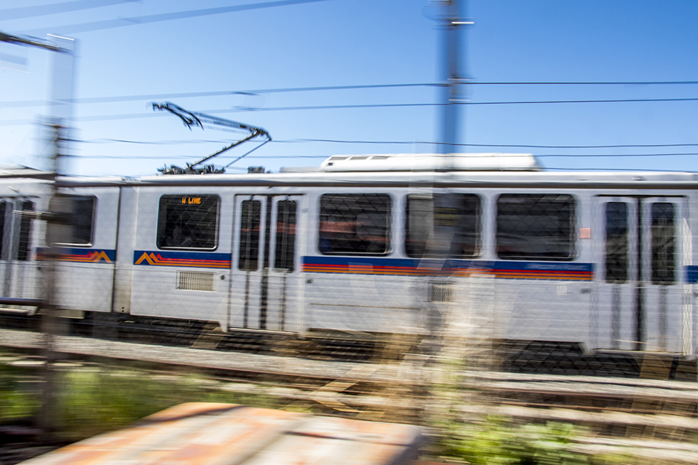 An RTD train whizzes by Strange Craft Beer Company's patio, May 16, 2018. (Kevin J. Beaty/Denverite)