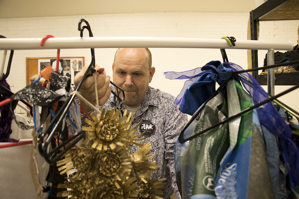 Rex Fuller, director of communications for The Center, checks out recycled garments in Lonnie Hanzon's Lakewood studio, May 29, 2018. (Kevin J. Beaty/Denverite)  lakewood; colorado; denverite; kevinjbeaty; sustainability; fashion; pridefest; pride; lgbtq; art;