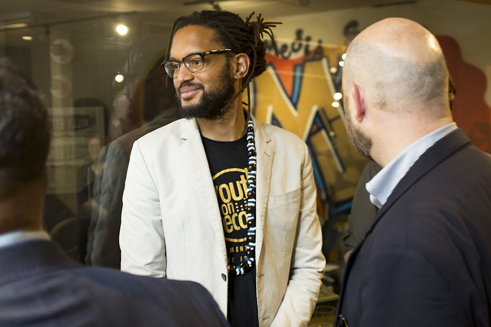 "Stephen Brackett, known as ""Brer Rabbit"" of the Flobots, meets with U.S. Department of Housing and Urban Development representatives inside Youth On Record, the music production nonprofit he helped found in Lincoln Park, May 23, 2018. (Kevin J. Beaty/Denverite)"