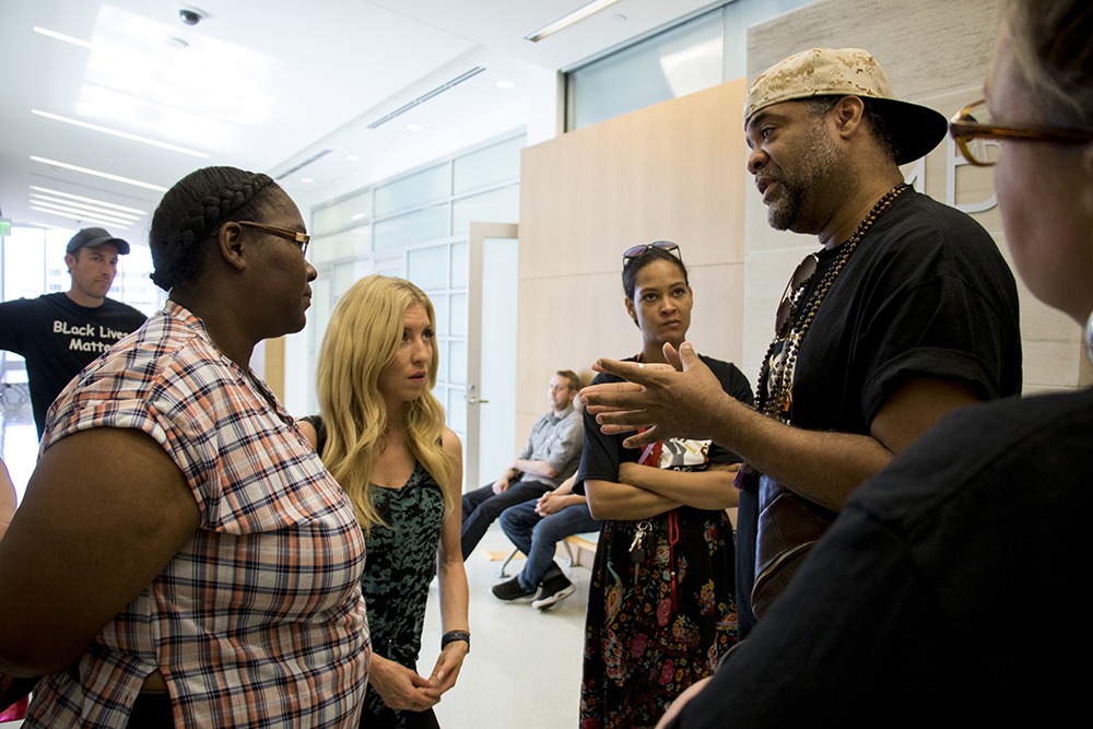 "Hasira ""Soul"" Ashemu (right) speaks to Sheena Gordon, whose daughters were involved in a fight that resulted in charges. Our Voice Our Schools activists have shown up to the Lindsey-Flanigan Courthouse to protest their appearance in court, May 24, 2018. (Kevin J. Beaty/Denverite)  denver; colorado; denverite; kevinjbeaty; lindsey-flanigan courthouse; criminal justice; school to prison pipeline;"