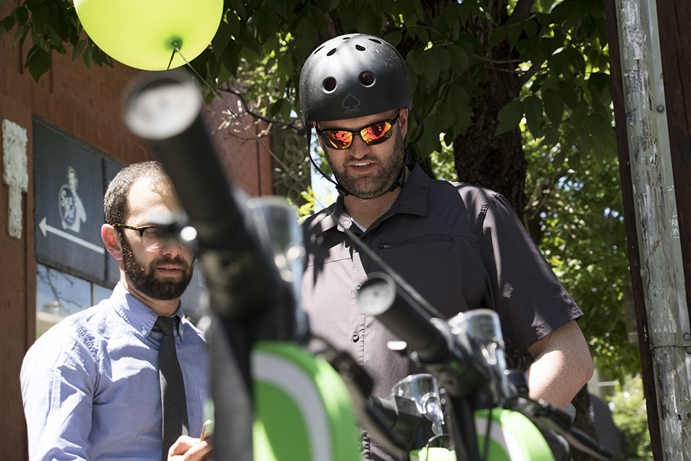City Councilman Jolon Clark checks out Lime's new dockless electric scooters outside of Mutiny Information Cafe, May 25, 2018. (Kevin J. Beaty/Denverite)  denver; colorado; denverite; transportation; lime; south broadway; kevinjbeaty; scooters;