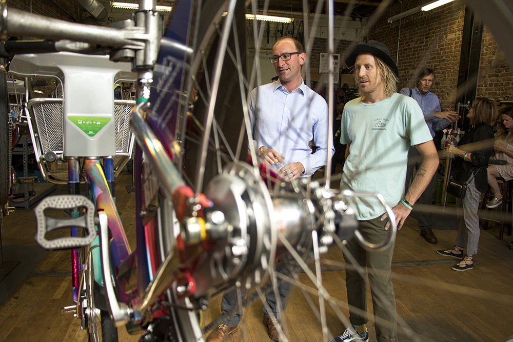 Artist Pat Milbery (right) chats with Nick Bohnenkamp, Executive Director of Denver B-Cycle. Denver B-Cycle and Kaiser Permanente unveil four hand-painted bikes at their headquarters on Larimer Street, May 31, 2018. (Kevin J. Beaty/Denverite)  denver; colorado; denverite; b-cycle; bikes; bicycles; rino; five points; transportation; art; public art; kevinjbeaty;